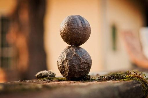 balanced stone ball sculpture on mossy surface